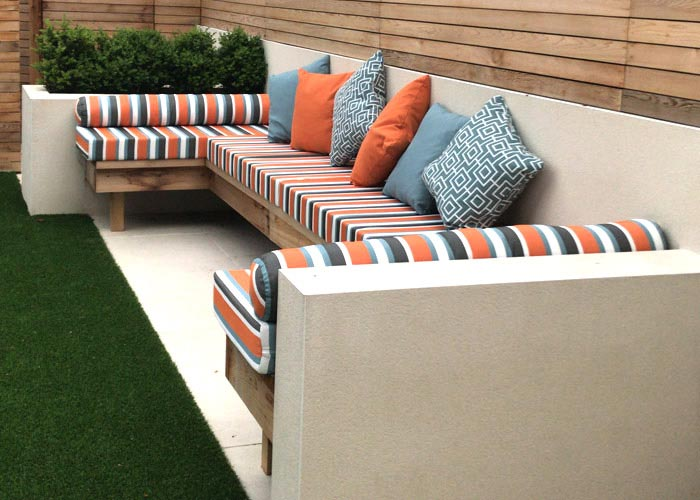 Co-ordinating striped and patterned outdoor chair and scatter cushions for a garden seating area